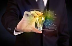 Businessman holding glowing glass light bulb Stock Image