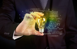 Businessman holding glowing glass light bulb Stock Photos