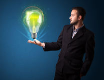 Businessman holding glowing lightbulb in his hand. Young businessman holding glowing lightbulb in his hand Stock Photography
