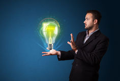 businessman holding glowing lightbulb Royalty Free Stock Image