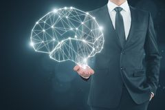 Artificial intelligence and future concept. Businessman holding glowing polygonal brain on dark background. Artificial intelligence and future concept. 3D Stock Images