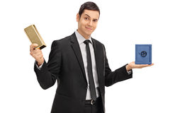 Businessman holding a gold bar and a safe. Young confident businessman holding a bar of gold and a small blue safe isolated on white background Royalty Free Stock Photos