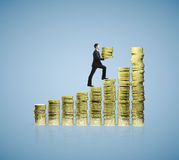 Businessman holding gold coins. Businessman climbing up on chart of gold coins Royalty Free Stock Photos