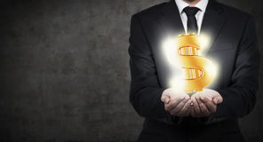 Businessman holding gold dollar Royalty Free Stock Image