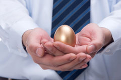Businessman holding gold egg Stock Photography
