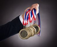 Businessman holding gold medals stock photos