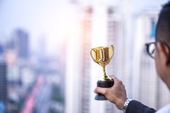 Businessman holding gold trophy, Business winner award. Hand of businessman president holding gold trophy on the top building, Business winner award stock photo