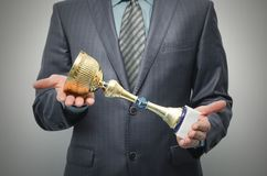 Golden award cup in the winner hands. royalty free stock photo