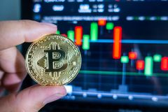 Businessman holding Golden Bitcoin in front of laptop with stock. Exchange graph background. Digital money concept Royalty Free Stock Photos