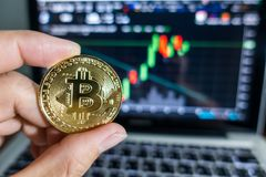 Businessman holding Golden Bitcoin in front of laptop with stock. Exchange graph background. Digital money concept Royalty Free Stock Images