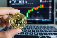 Businessman holding Golden Bitcoin in front of laptop with stock. Exchange graph background. Digital money concept Royalty Free Stock Photography
