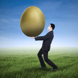 Businessman holding a golden egg Stock Photos