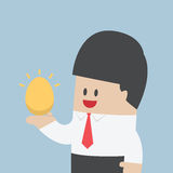 Businessman holding golden egg in his hand Royalty Free Stock Photo