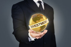Businessman holding a golden globe with investment Stock Images