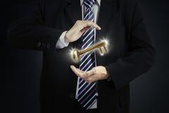 Businessman holding golden key Royalty Free Stock Images
