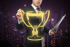Businessman holding golden winner's cup Royalty Free Stock Images