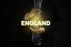 Businessman holding a golden word of England Stock Images