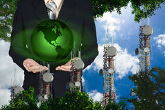 Businessman holding green earth planet in hand standing on blue sky and cloud background with telecommunication towers Royalty Free Stock Photography