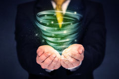 Businessman holding green tornado Stock Images