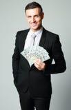 Businessman holding group of dollar bills Stock Images