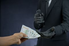 Businessman holding guns plundered money from someone. Stock Images