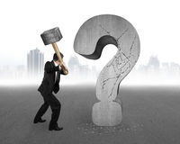 Businessman holding hammer cracked question mark with gray citys Stock Photo