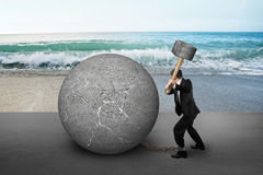 Businessman holding hammer hitting cracked concrete ball with se Royalty Free Stock Photo