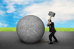 Businessman holding hammer hitting cracked concrete ball with sk Stock Images