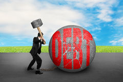 Businessman holding hammer hitting cracked DEBT ball with sky cl Stock Photo