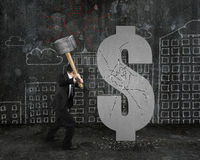 Businessman holding hammer hitting cracked dollar sign with buil Royalty Free Stock Photography