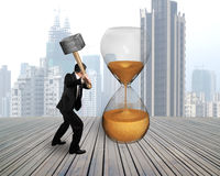 Businessman holding hammer to hit hour glass Stock Photo