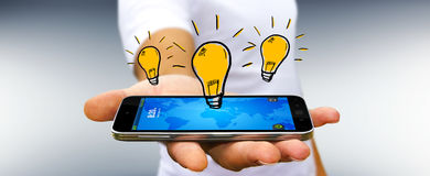Businessman holding hand drawn lightbulb. Over his mobile phone Royalty Free Stock Image