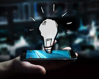 Businessman holding hand drawn lightbulb. Over his mobile phone Stock Photos