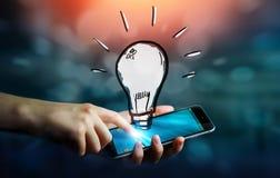 Businessman holding hand drawn lightbulb. Over his mobile phone Stock Image
