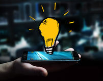 Businessman holding hand drawn lightbulb. Over his mobile phone Stock Photography