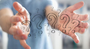 Businessman holding hand drawn question marks in his hand Royalty Free Stock Image