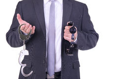 Businessman holding handcuffs and ball gag. Isolated on white background Stock Photos