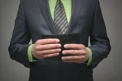 Businessman holding in hands a black leather wallet, close up photo. Royalty Free Stock Photo