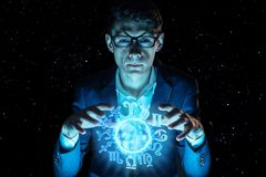 Businessman holding hands over the magic sphere with a horoscope to predict the future. Astrology as a business. Man businessman holding hands over the magic royalty free stock photos