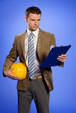 Businessman holding hardhat and looking at clipboard Stock Photography