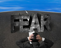 Businessman holding head facing fear concrete word on asphalt ro Stock Photography