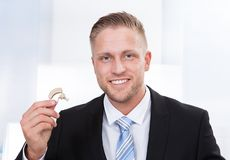 Businessman holding hearing aid Stock Image