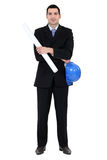 Businessman holding helmet and blueprints Stock Photography
