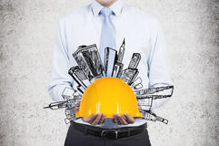 Businessman holding helmet. With drawing skyscraper Royalty Free Stock Photography