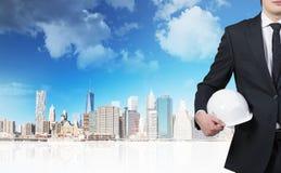 Businessman holding helmet. On skyscraper background Stock Images