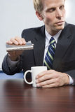 Businessman holding hip flask Royalty Free Stock Images