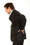 Businessman holding his hand at his aching back. Young businessman holding his hand at his aching back isolated on white royalty free stock photo