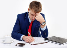 Businessman holding his hand near the head. Pen writes in a notebook. Hard thinking Stock Images
