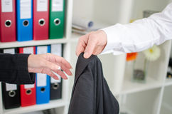 Businessman holding his jacket to his assistant Royalty Free Stock Images
