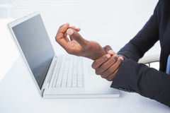 Businessman holding his sore wrist from typing. In his office stock images